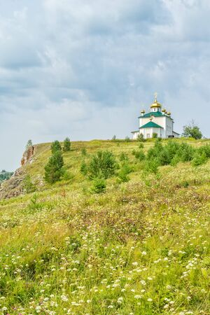 Landscape with the Church of the Kazan Icon of the Mother of God against a cloudy sky. Russia, Ural 写真素材