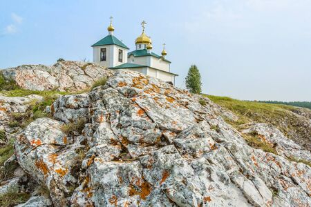 Landscape with the Church of the Kazan Icon of the Mother of God on the cliff against a blue sky. Russia, Ural 写真素材