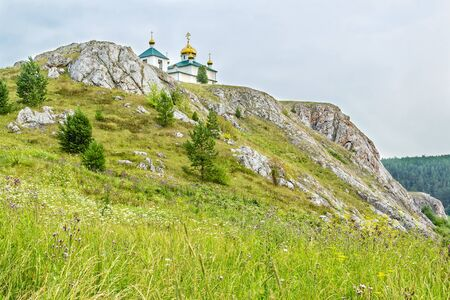 Landscape with the Church of the Kazan Icon of the Mother of God on the cliff against a blue sky. Russia, Ural Mountains
