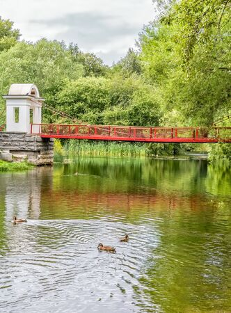 Suspension bridge and ducks on the pond in a park on a summer day. Park of the Rastorguev-Kharitonov estate, Russia, Yekaterinburg