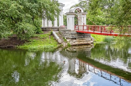 Suspension bridge and rotunda on a small island on a pond in the park on a summer day. Park of the Rastorguev-Kharitonov estate, Russia, Yekaterinburg 写真素材