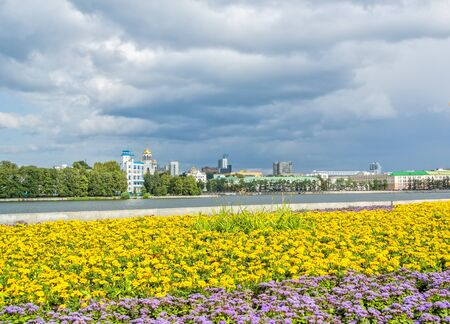 Scenic cityscape with flowerbed on the embankment of the city pond of Yekaterinburg, Russia