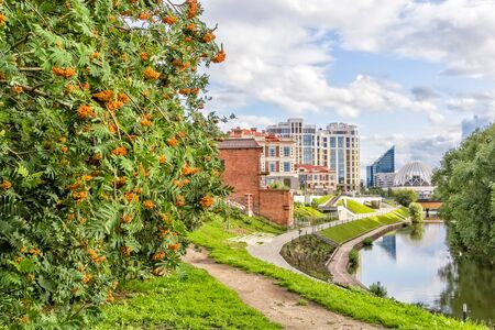 Scenic cityscape with rowan and embankment of the Iset River, Yekaterinburg, Russia