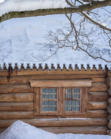 Log cabin in a winter day after a snowfall, close-up