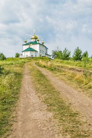 Landscape with a country road along the mountainside to the Church of the Kazan Icon of the Mother of God against the background of a cloudy sky. Russia, Ural, village Aramashevo Reklamní fotografie