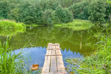 Fishing spot with wooden gangway on the river on a summer day