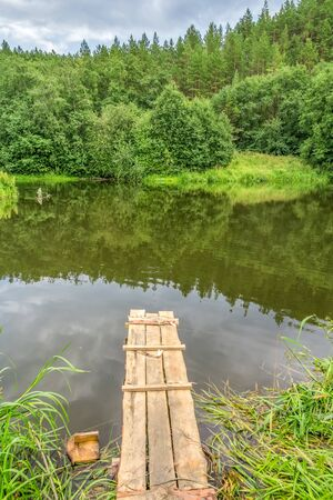 Fishing spot with wooden gangway on the lake on a summer day Reklamní fotografie