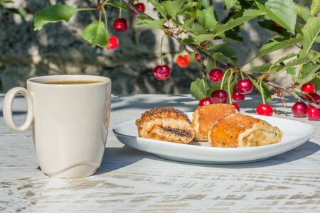 Breakfast with coffee and pastries in the garden under the cherry tree in the sunny summer morning, close-up