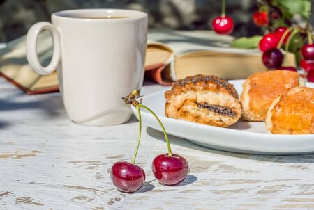 Breakfast with coffee and pastries in the cherry orchard on a sunny summer morning, close-up