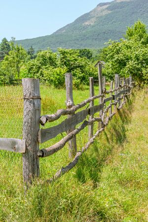 Wooden fence in the field against the background of the garden, mountains and blue sky