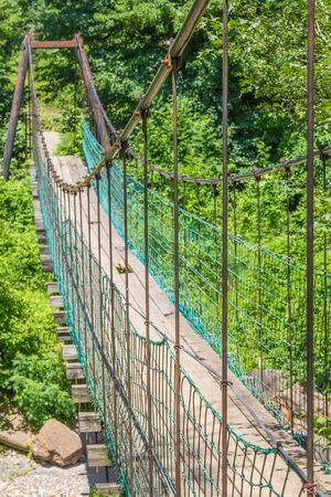Picturesque suspension bridge on a mountain river, close-up