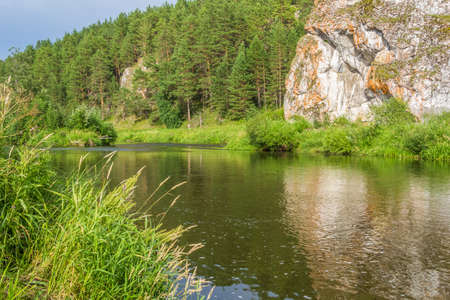 Picturesque summer landscape with forest, rock and reflection in the river on a sunny summer day Reklamní fotografie