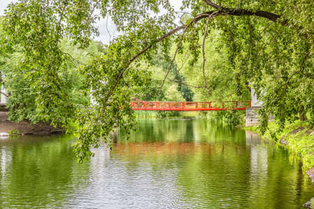 Landscape with poplar branch and suspension bridge in the park. Park of the Rastorguev-Kharitonov estate, Russia, Yekaterinburg