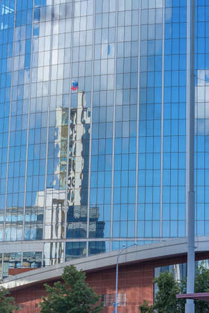 Fragment of a glass panoramic facade of a skyscraper with reflection of surrounding buildings and blue sky with a white cloud, Yekaterinburg, Russia