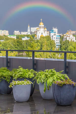 Scenic city view from the terrace with floral containers. Rainbow in the dark sky after a thunderstorm. Yekaterinburg, Russia Reklamní fotografie