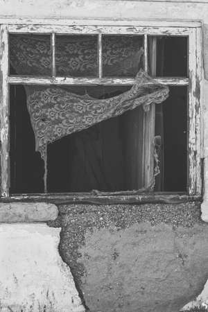 Old wooden window in a ruined house. Black and white photo. Retro style Reklamní fotografie