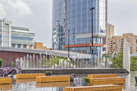 Terrace with fountain and wooden benches in the rain. Yekaterinburg city center, Russia