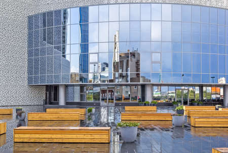 Terrace with wooden benches and flower containers and a glass facade with a reflection of the surroundings. Public, cultural and education center - Yeltsin Center. Russia, Yekaterinburg