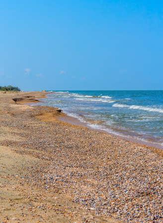 Sunny summer day on the beach by the sea against the blue sky