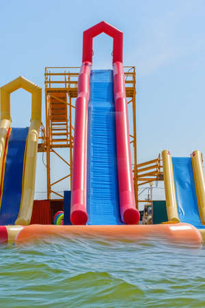 Attraction with inflatable slides by the sea against the blue sky Reklamní fotografie