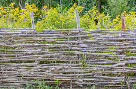 Picturesque wattle fence of twigs with bark around a flowering garden, close-up