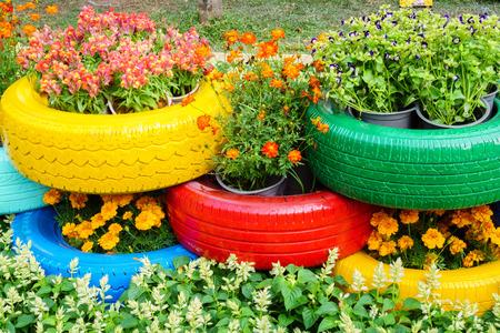 jardines con flores: Las flores de colores y ollas de neum�ticos Foto de archivo