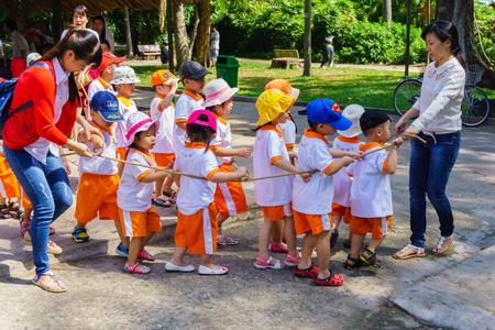 zoologico: Los ni�os y maestros que juegan en el parque zool�gico