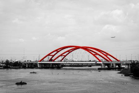 monochromatic: Landscape of red bridge and plane on a monochromatic background