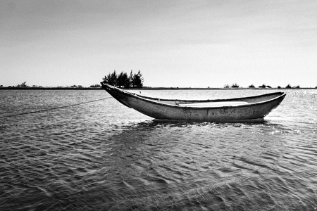 ange: Alone boat in the river. Black and white