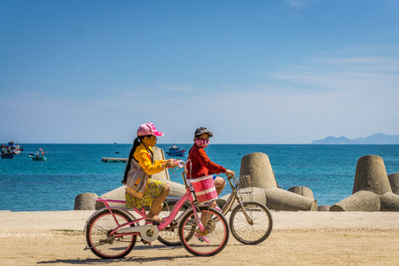 Two child driving thier bicycle in beach