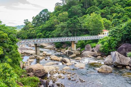 Landscape of steel bridge on stream Stock Photo