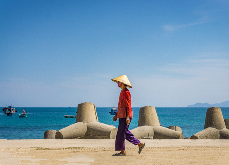 Old woman is walking in the beach