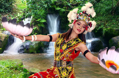 Sarawak, Malaysia - August 04, 2019: Iban traditional dance performer with full tribe costume dancing by the waterfall in Sarawak Malaysia