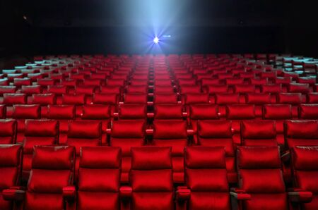Red cinema seats with projector bright lights in background