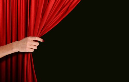 Hand opening red curtain over black background 免版税图像