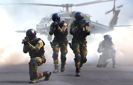 Special force assault team in a mission with helicopter background