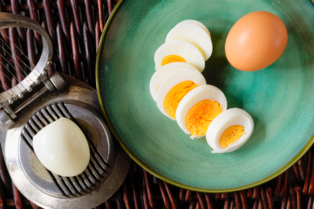 Hard-boiled egg cut and piled on egg slicer and full egg with shell on green plate or dish. Stock Photo