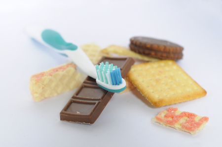 Toothbrush, cookies and chocolates on white background. Dental health concept