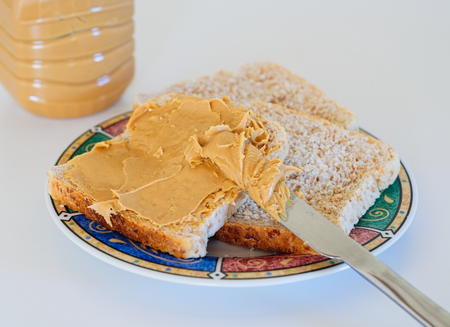 Creamy peanut butter spread on toast bread on the plate, knife and peanut butter jar