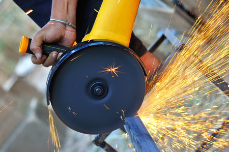 Sawing a metal with sparkles flying around. Metallurgy work