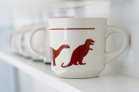 Cups lining up with dinosaurs printed on them. Leader and follower, rules and management concept Banco de Imagens