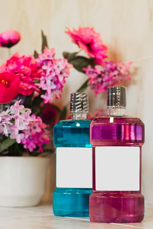 Colorful bottles of mouthwash or soap next to a colorful artificial flower pot in the bathroom