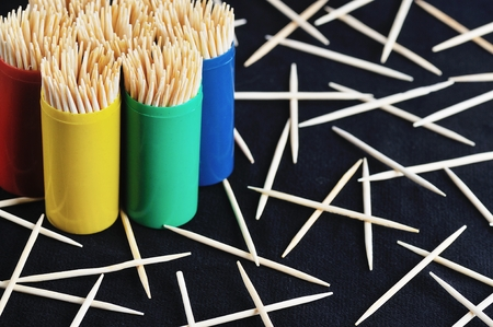 toothpick: toothpicks in colorful plastic container on plain, black background