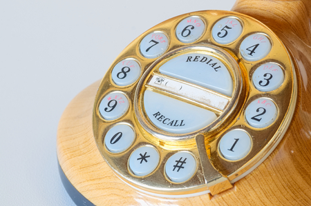Close up of the dial number of an old style phone  in plastic like wood and golden dial