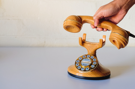 Hand and old style in plastic like wood and golden dial phone pretending to make a call or hang up