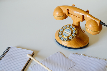 Old style phone in plastic like wood and golden dial with pencil and notebook Stock Photo