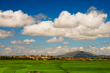 Typical landscape of the highland in central Madagascar, ruins, square houses, rice paddy field, dramatic clouds