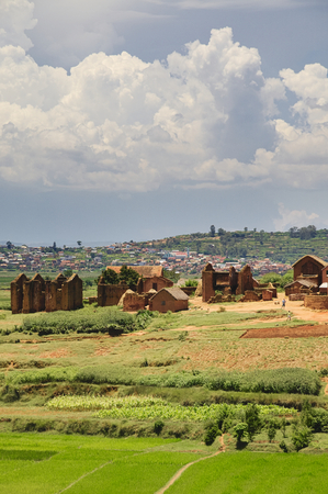 typical: Typical landscape of the highland in central Madagascar, ruins, square houses, rice paddy field, dramatic clouds