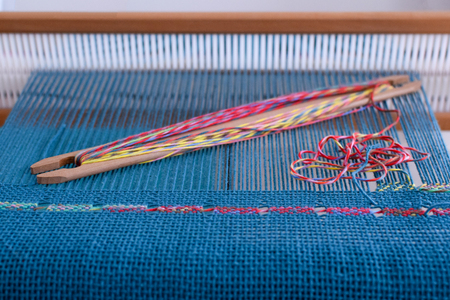 Tissage de dentelle espagnole sur métier à lisses rigide avec chaîne bleue et trame colorée