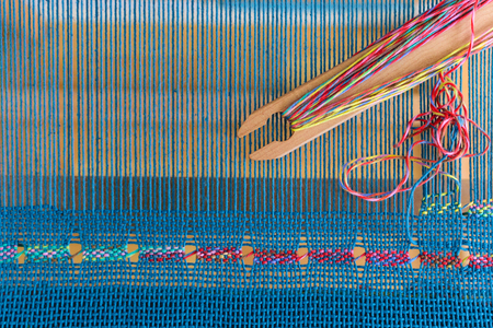 Spanish lace weaving on rigid heddle loom with blue warp and colorful weft Banco de Imagens